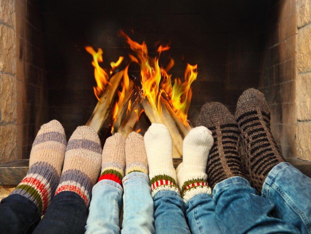 family wearing woolen socks near the fireplace
