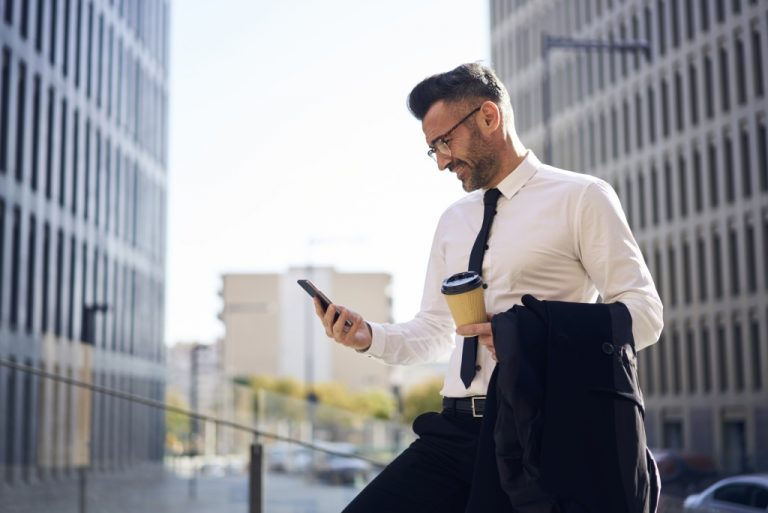 man holding coffee and phone