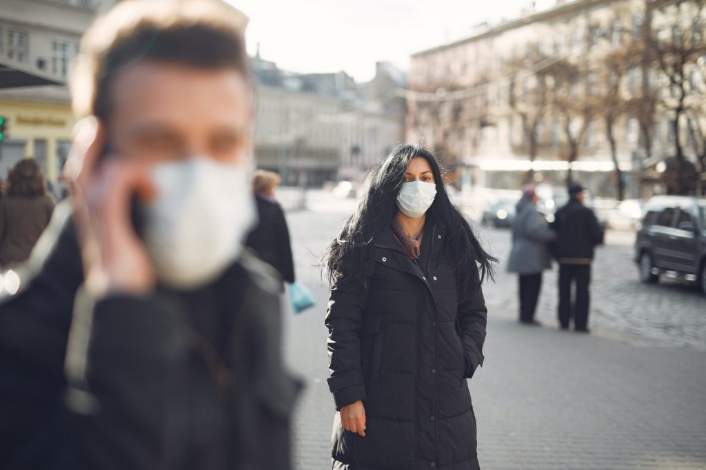 woman standing outside wearing a mask