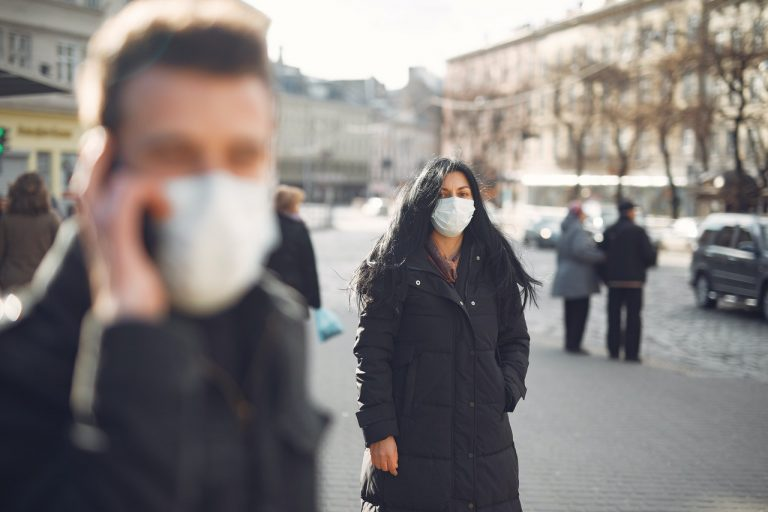 woman standing outside wearing a mask