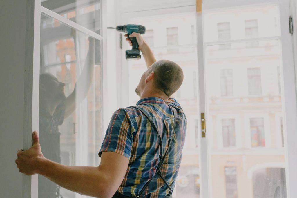 man replacing a window panel